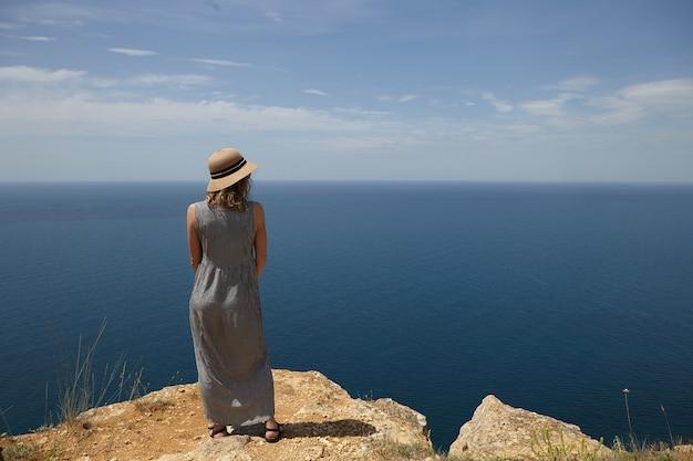 Rückansicht der schönen frau, die strohhut und sommermaxikleid trägt, die oben auf berg steht und herrliches endloses meer vor ihr betrachtet. urlaubs-, reise- und küstenkonzept