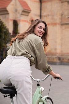 Rückansicht der schönen smiley-frau, die ihr fahrrad draußen reitet