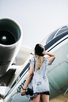 Rückansicht der schönen touristischen frau mit alten film vintage kamera posiert in der nähe des flugzeugs