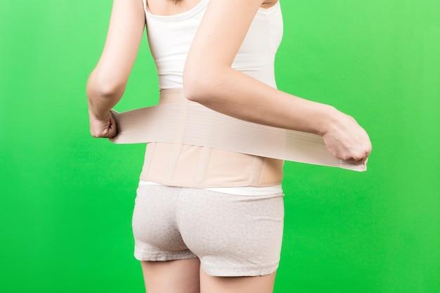 Rückansicht der schwangeren frau, die einen stützverband anlegt, um rückenschmerzen auf grünem hintergrund mit kopienraum zu reduzieren. abgeschnittenes bild des orthopädischen bauchstützgürtelkonzepts.