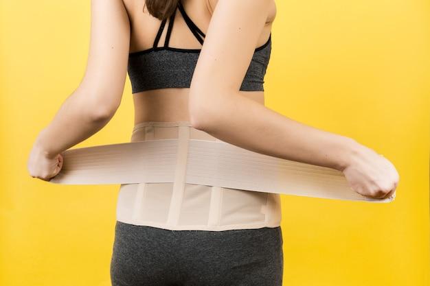 Rückansicht der schwangeren frau, die orthopädisches korsett anzieht, um die rückenschmerzen an der gelben oberfläche mit kopierraum verschwinden zu lassen