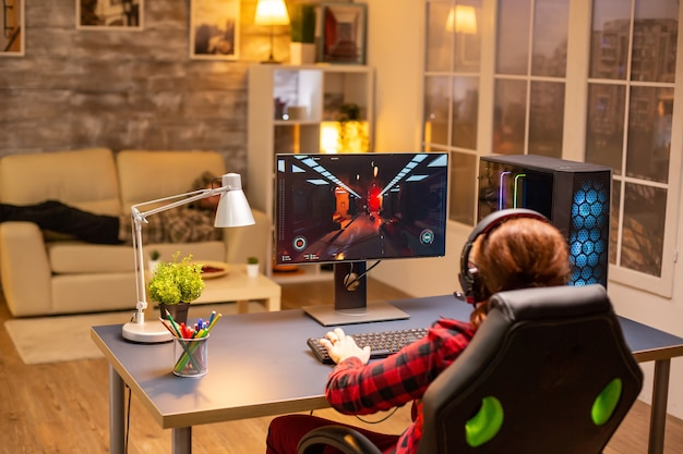 Rückansicht der spielerin, die spät nachts im wohnzimmer auf einem leistungsstarken computer-pc spielt.