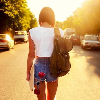Rückansicht der teenager mit rucksack und skateboard bei sonnenuntergang