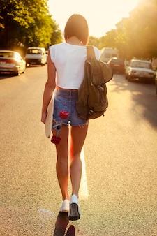 Rückansicht der teenager mit skateboard in der hand bei sonnenuntergang