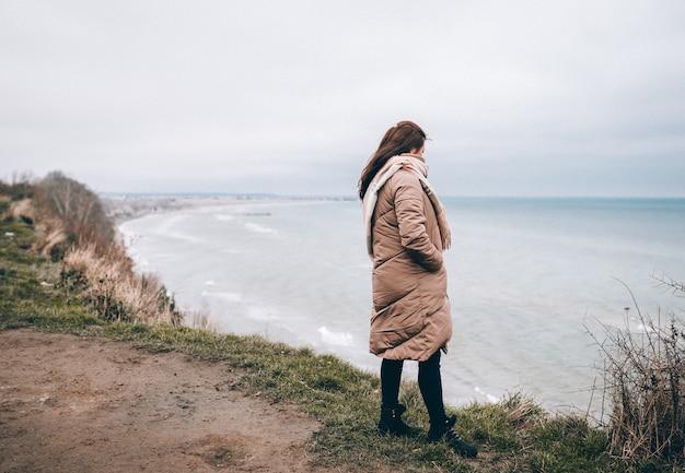 Rückansicht der traurigen alleinigen frau in der warmen winterkleidung