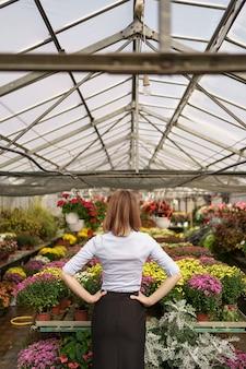 Rückansicht der unternehmerin, die das ergebnis ihrer arbeit beobachtet. gewächshausbesitzer, der verschiedene arten von blumen betrachtet