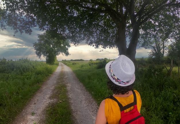 Rückansicht der wandernden frau mit sommerhut