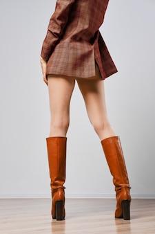 Rückansicht der weiblichen beine in den braunen stiefeln und in den weißen strumpfhosen mit punktmuster
