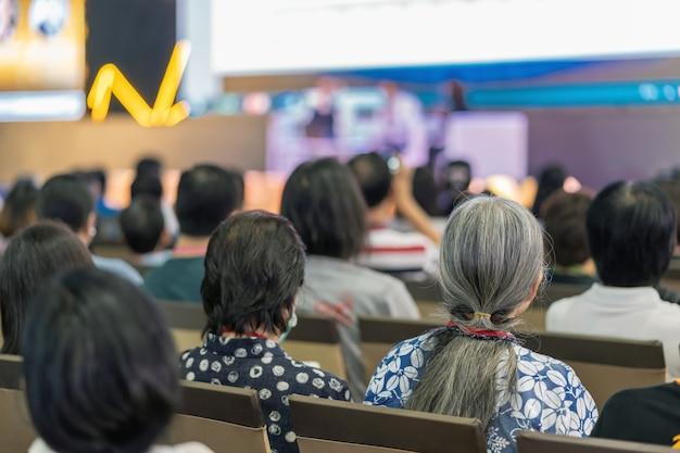 Rückansicht der zuhörerschaft zuhörende sprecher auf der bühne im konferenzsaal oder im seminar