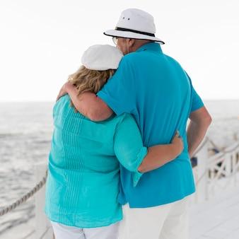 Rückansicht des älteren touristenpaares, das am strand umarmt wird