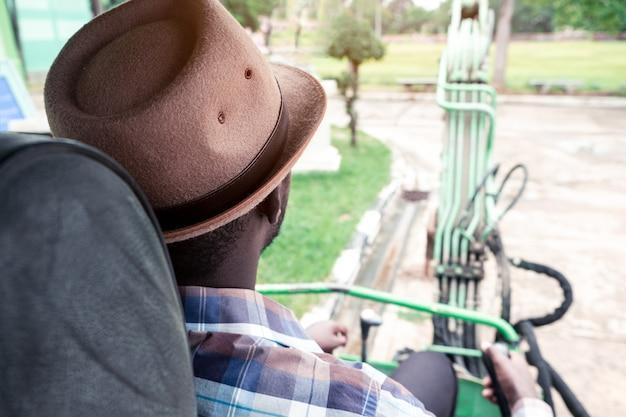 Rückansicht des afrikanischen arbeiters, der schweren baumaschinen-baggerlader fährt