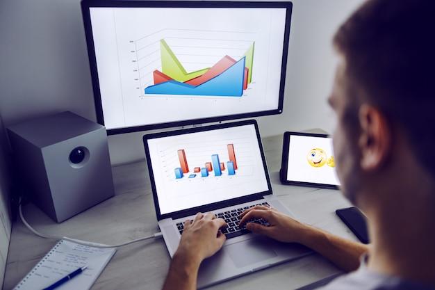 Rückansicht des arbeitenden mannes bei der analyse der erhöhung des einkommens des monatsgehalts. die hände sind auf der tastatur. auf den displays sind diagramme.