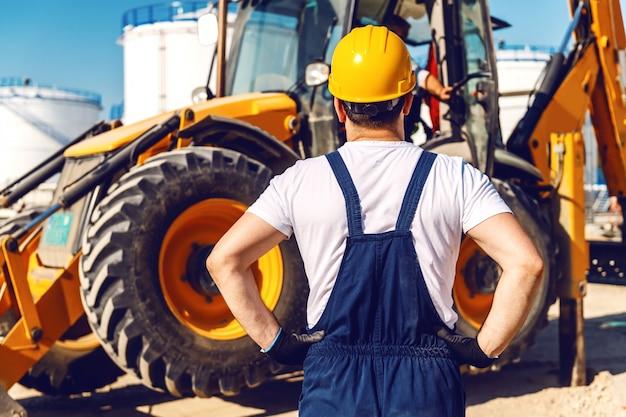 Rückansicht des arbeiters in uniform, der bagger beim stehen in der raffinerie betrachtet.