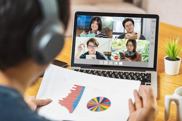 Rückansicht des asiatischen geschäftsmannes, der die datendiagrammanalyse mit teamarbeitskollegen präsentiert