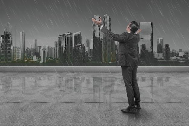 Rückansicht des asiatischen geschäftsmannes, der mit erhobener hand auf dem dach mit regnerischem hintergrund steht