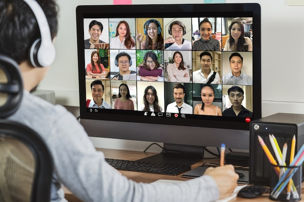 Rückansicht des asiatischen geschäftsmannes, der über videokonferenz mit kollegen arbeitet und online-meetings macht