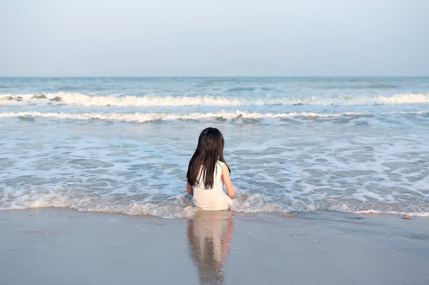 Rückansicht des asiatischen kindes, das auf dem sandstrand sitzt