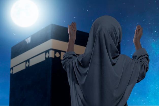 Rückansicht des asiatischen muslimischen kleinen mädchens in einem schleier, der vor der kaaba mit dem hintergrund der nachtszene betet und erhobene hände betet