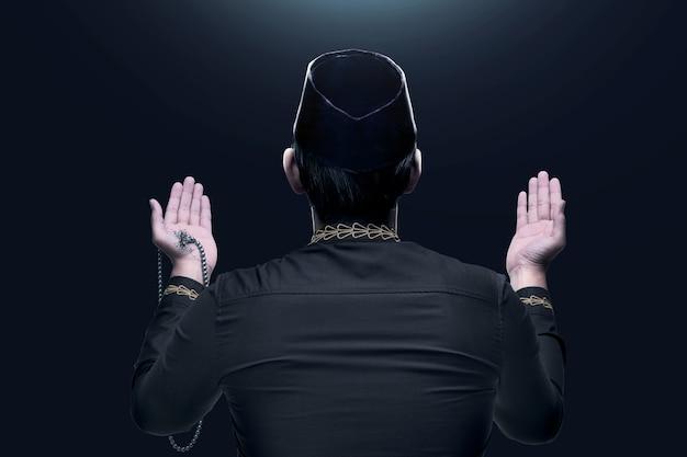 Rückansicht des asiatischen muslimischen mannes, der mit gebetsperlen auf seinen händen betet
