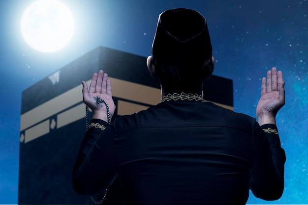 Rückansicht des asiatischen muslimischen mannes, der mit gebetsperlen mit kaaba-ansicht und nachtszenenhintergrund steht und betet