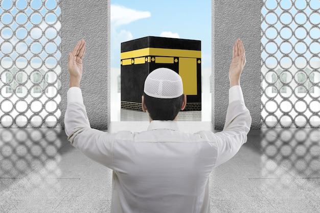 Rückansicht des asiatischen muslimischen mannes, der mit kaaba-ansicht und blauem himmelshintergrund steht und betet