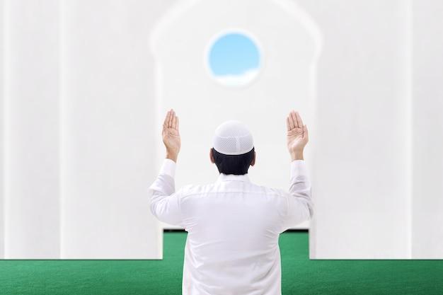 Rückansicht des asiatischen muslimischen mannes, der sitzt, während erhobene hände und auf der moschee beten