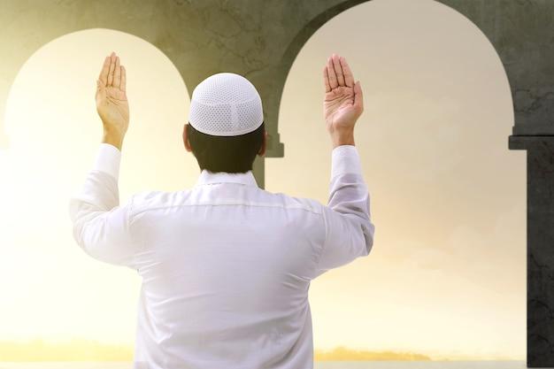 Rückansicht des asiatischen muslimischen mannes stehend, während erhobene hände und auf der moschee betend