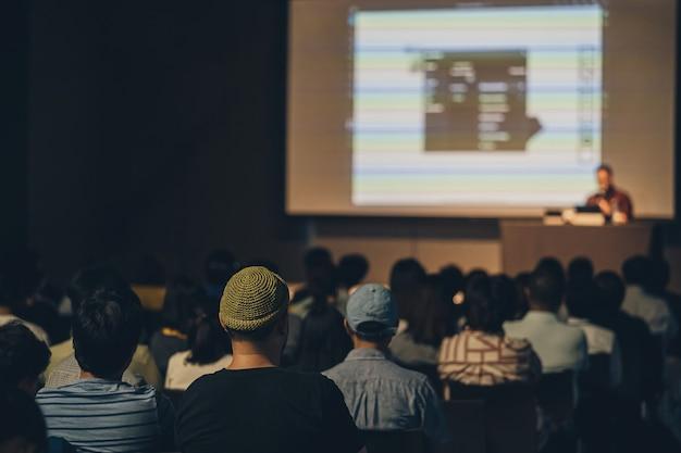 Rückansicht des asiatischen publikums, das im seminar auf der bühne spricht und zuhört