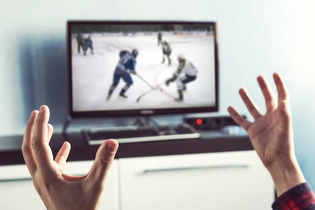 Rückansicht des aufregungsmannes mit gestikulierenden händen, wie er zu hause eishockey im fernsehen sieht. rückansicht des mannes sport im fernsehen gucken. ein begeisterter fan feuert für seine lieblingsmannschaft an