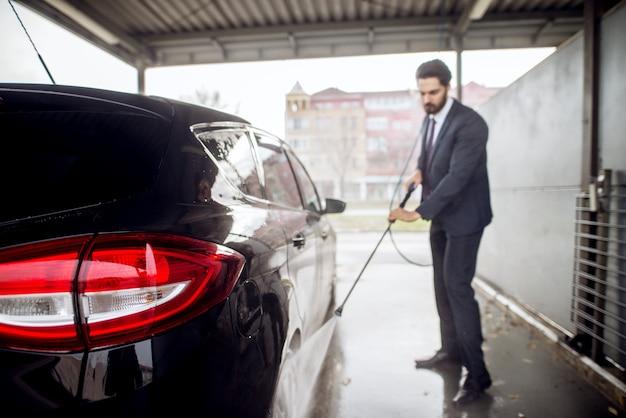 Rückansicht des autos und des eleganten jungen geschäftsmannes in einem anzug, der reifen des autos mit einer wasserpistole auf selbstbedienungswaschwagenstation wäscht.