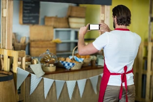 Rückansicht des bäckereipersonals, das bäckereisnacks und brot auf der theke fotografiert
