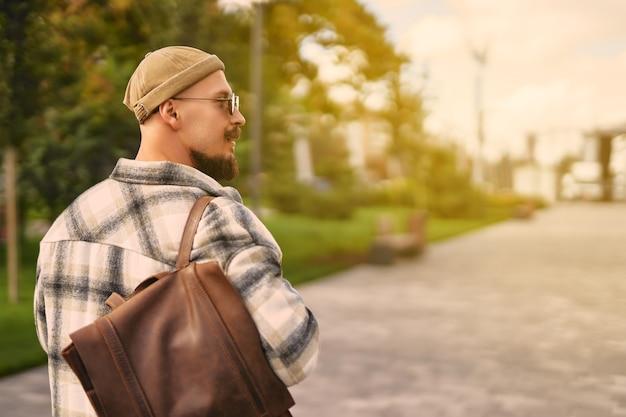 Rückansicht des bärtigen hipster-studenten sieht seitlich aus, während er im ruhetag des städtischen stadtparks spazieren geht