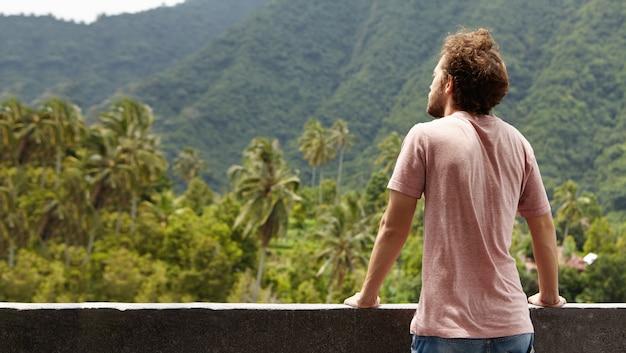 Rückansicht des bärtigen reisendenmannes, der schönheiten des grünen waldes betrachtet, während urlaub in heißem land verbringt, malerische landschaft und frische bergluft genießt