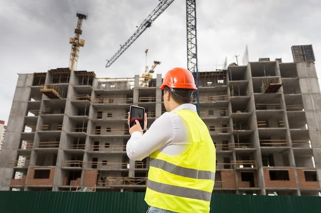 Rückansicht des bauinspektors, der ein digitales tablet hält und die baustelle inspiziert