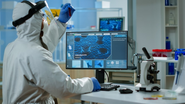 Rückansicht des chemikers im overall, der auf dem computer tippt, der die impfstoffentwicklung in einem ausgestatteten labor analysiert. ärzteteam im psa-anzug, das high-tech zur erforschung der behandlung gegen das covid19-virus verwendet