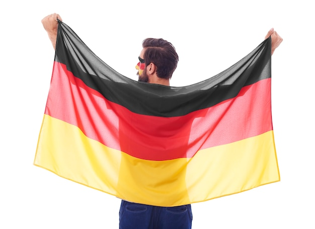 Rückansicht des deutschen fan, der eine flagge schwenkt