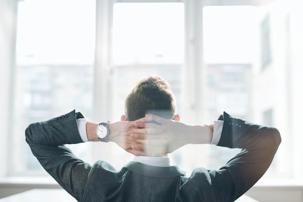 Rückansicht des eleganten geschäftsmannes in der abendgarderobe, der seine hände auf hinterkopf hält, während er vor bürofenster sitzt