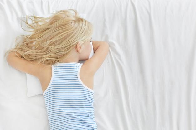 Rückansicht des entzückenden blonden mädchens, das gestreiftes t-shirt trägt, gesunden schlaf hat, auf bauch auf weißem kissen liegt und von etwas träumt. ruhiges sorgloses kleines kind, das nach der schule im bett schläft