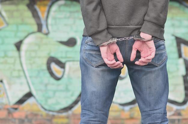 Rückansicht des festgenommenen und mit handschellen gefesselten täters gegen die gr