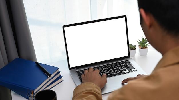 Rückansicht des freiberuflichen jungen mannes, der an einem komfortablen arbeitsplatz sitzt und einen laptop verwendet.
