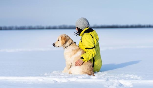 Rückansicht des freundlichen hundes und der frau, die auf schneebedecktem feld sitzen sitting