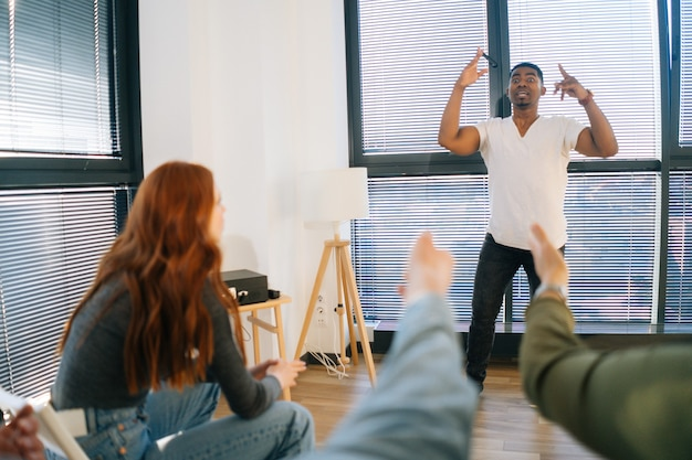 Rückansicht des fröhlichen afroamerikanischen mannes, der scharaden mit freunden spielt, die pantomime am fenster im hellen büroraum zeigen. diverse multiethnische kollegen, die während des teambuildings in aktiven spielen spielen