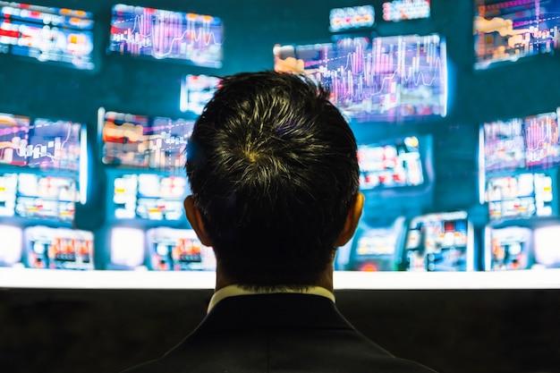 Rückansicht des geschäftsmannes, der auf den monitor mit börsendiagramm schaut Premium Fotos