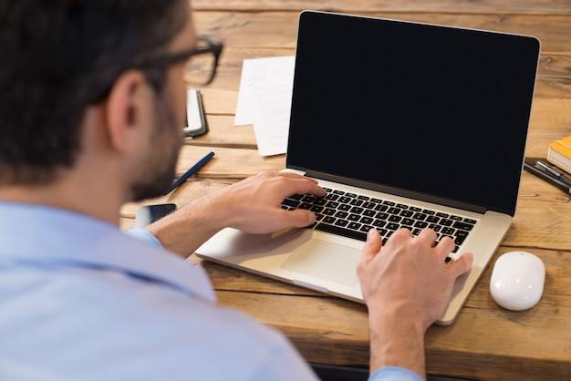 Rückansicht des geschäftsmannes, der vor laptop-bildschirm sitzt. mann, der auf einem modernen laptop in einem büro tippt. junger student, der am computer tippend am holztisch tippt.