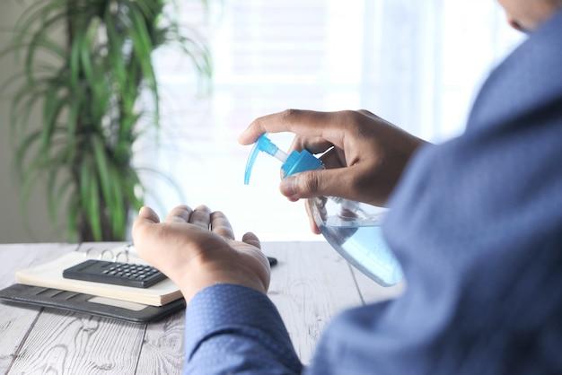 Rückansicht des geschäftsmannes unter verwendung des desinfektionsgels auf schreibtisch