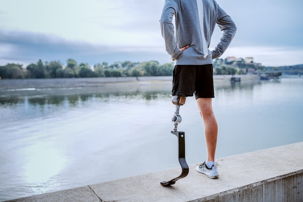 Rückansicht des gesunden kaukasischen behinderten mannes in sportbekleidung und mit künstlichem bein, das auf kai mit händen auf hüften steht.