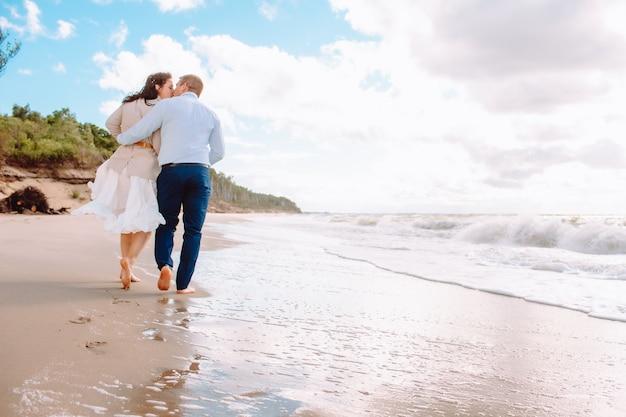 Rückansicht des glücklichen gerade verheirateten paares mittleren alters gehen am strand gegen blauen himmel mit wolken und haben spaß am sommertag.