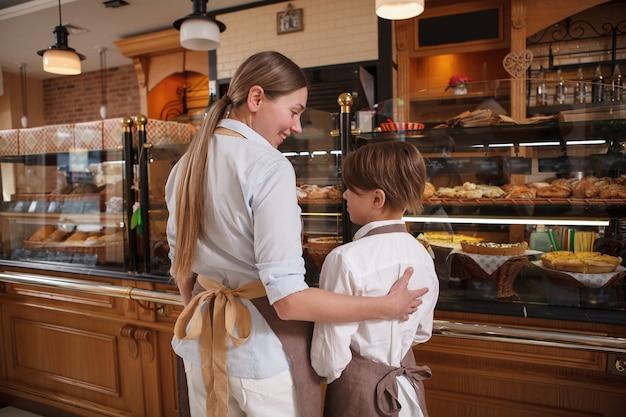 Rückansicht des glücklichen professionellen bäckers der mutter, der ihren kleinen sohn umarmt und zusammen bei ihrer familienbäckerei arbeitet