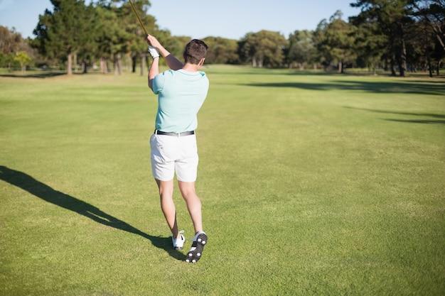Rückansicht des golfers, der schießt