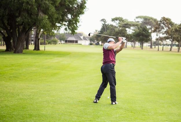 Rückansicht des golfers, der seinen golfschläger anhebt